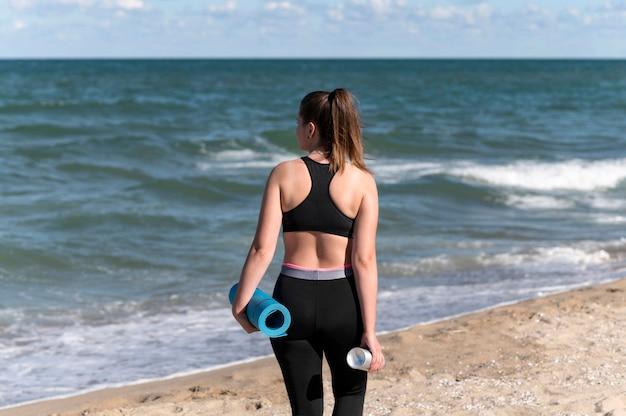 Mulher de costas segurando tapete de ioga