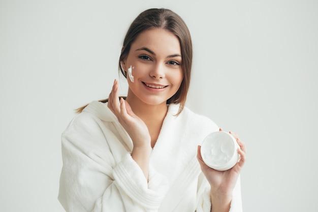 Mulher de creme facial aplicando crean no retrato natural da pele. tiro do estúdio.