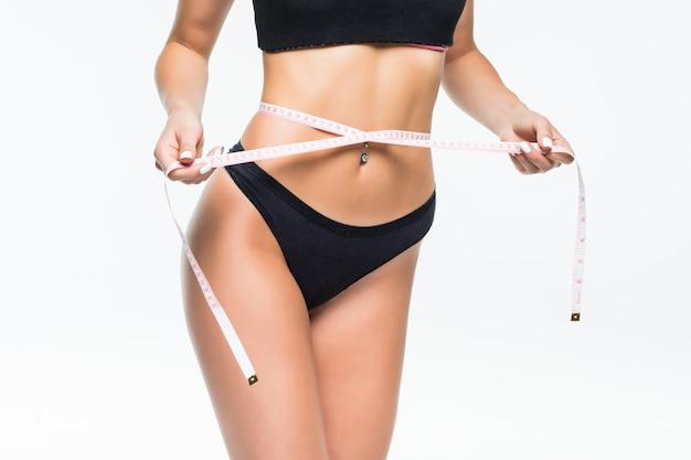 Mulher de cueca preta, medindo a cintura com fita métrica isolada na parede branca