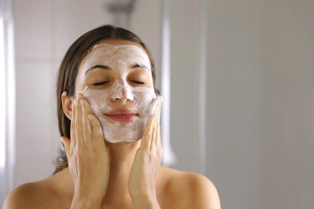 Mulher de cuidados com a pele lavando o rosto com espuma de sabão facial na pele
