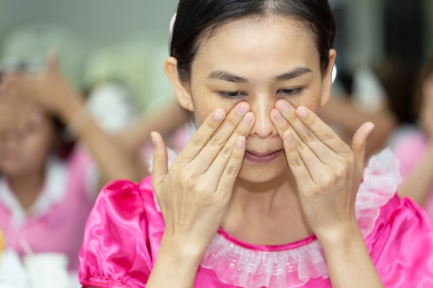 Mulher de cuidados com a pele lavando o rosto no chuveiro, espuma de sabão esfoliante facial na pele.