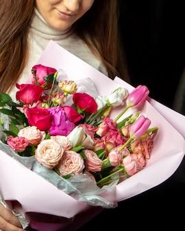 Mulher de decoração floral segurando boquet de tulipas rosas e rosas vermelhas
