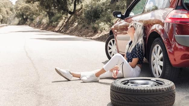 Mulher de desespero sentado perto do carro quebrado na estrada