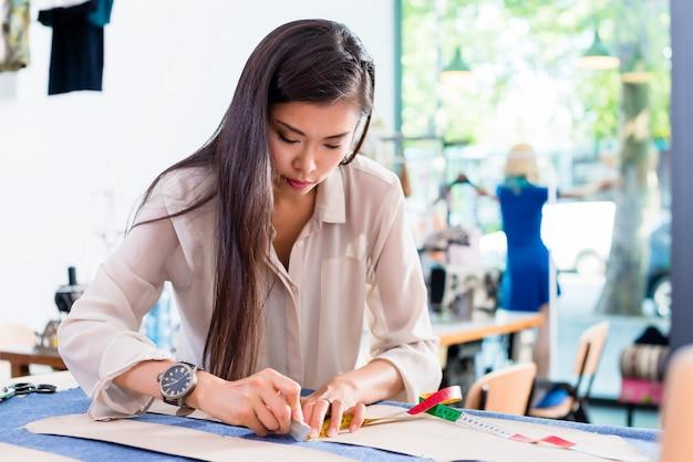 Mulher de designer de moda asiática esboça corte padrão