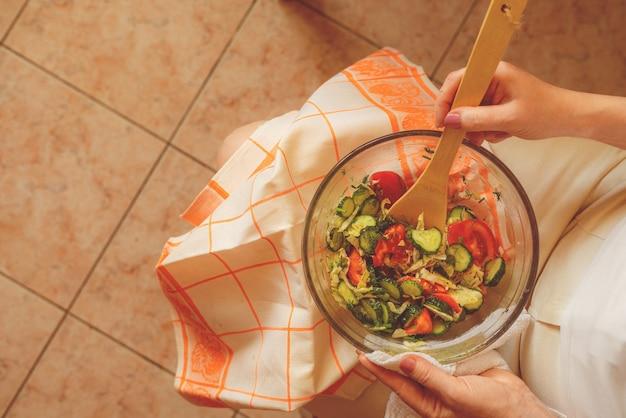 Mulher de dieta com prato de salada crua de joelhos. conceito de desintoxicação saudável