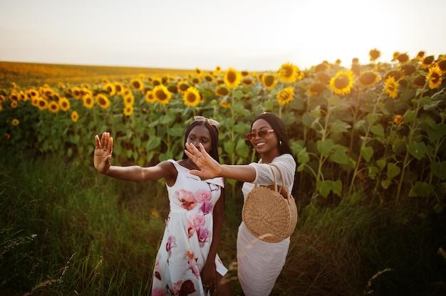 Mulher de dois amigos negros muito jovens usa pose de vestido de verão em um campo de girassol.