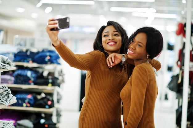 Mulher de dois modelos de vestido túnica marrom posou na loja de roupas boutique