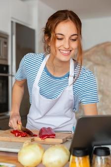 Mulher de dose média cortando pimenta