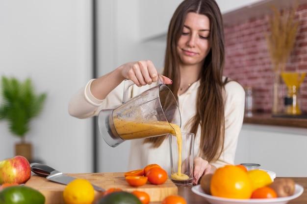 Mulher de dose média servindo smoothie