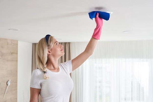 Mulher de empregada doméstica segurando a pilha de esfregão, limpando o teto da sala de estar. conceito de serviço de limpeza de casa.