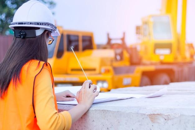 Mulher de engenheiro procurando construção. mulher, arquiteta, com, blueprint, medindo fita, e, whi