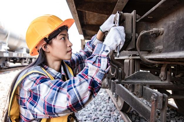 Mulher de engenheiros trabalhando no local da garagem do trem e usando uma chave inglesa para consertar o motor de tração do trem