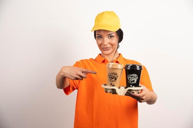Mulher de entrega apontando para xícaras de café para viagem na parede branca.