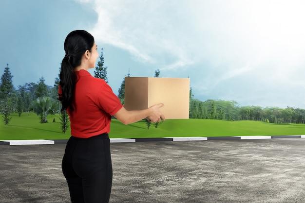 Mulher de entrega asiática feliz carregando o pacote