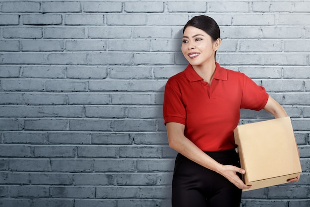 Mulher de entrega asiática sorridente carregando a parcela