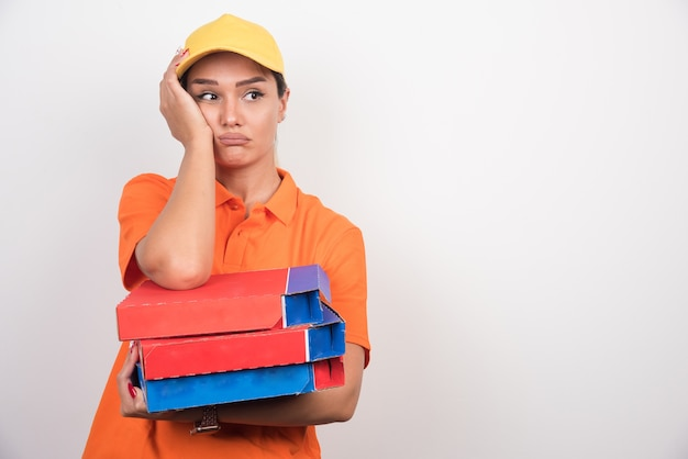 Mulher de entrega cansada segurando caixas de pizza.