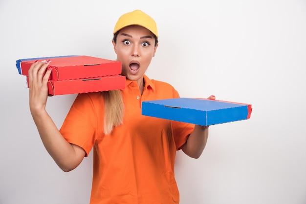 Mulher de entrega chocada segurando caixas de pizza.