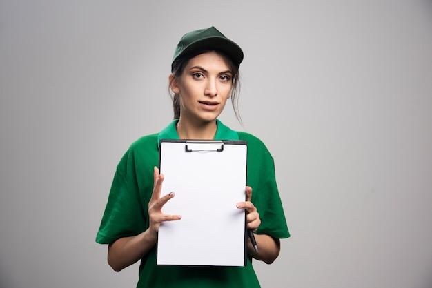 Mulher de entrega com prancheta posando