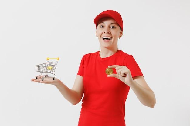 Mulher de entrega de boné vermelho, camiseta isolada no fundo branco. correio feminino segurando carrinho de empurrar de supermercado para fazer compras, bitcoin, moeda de metal de cor dourada. copie o espaço para anúncio.