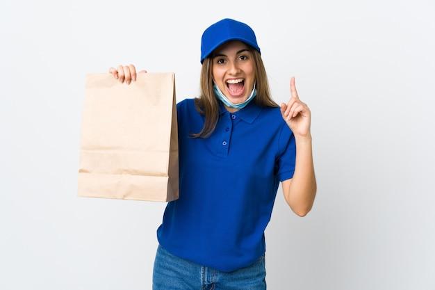 Mulher de entrega de comida e proteção contra o coronavírus com uma máscara sobre parede branca isolada apontando uma ótima idéia