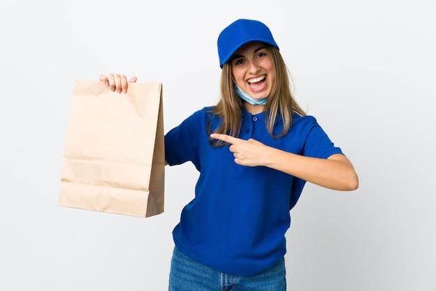 Mulher de entrega de comida e protegendo do coronavírus com uma máscara sobre parede branca isolada e apontando