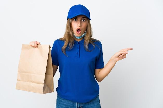 Mulher de entrega de comida e proteger do coronavírus com uma máscara sobre parede branca isolada surpreendeu e apontou o lado