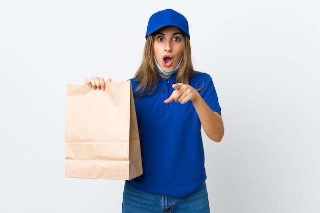Mulher de entrega de comida sobre parede branca surpreso e apontando a frente