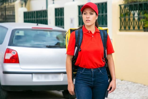 Mulher de entrega de conteúdo carregando bolsa térmica amarela. correio jovem de camisa vermelha à procura de endereço e entrega de pedido.