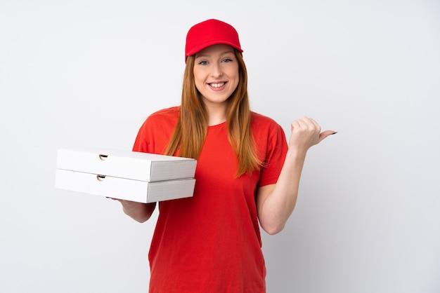 Mulher de entrega de pizza segurando uma pizza sobre parede rosa isolada, apontando para o lado para apresentar um produto