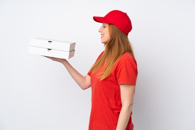 Mulher de entrega de pizza segurando uma pizza sobre parede rosa isolada com expressão feliz