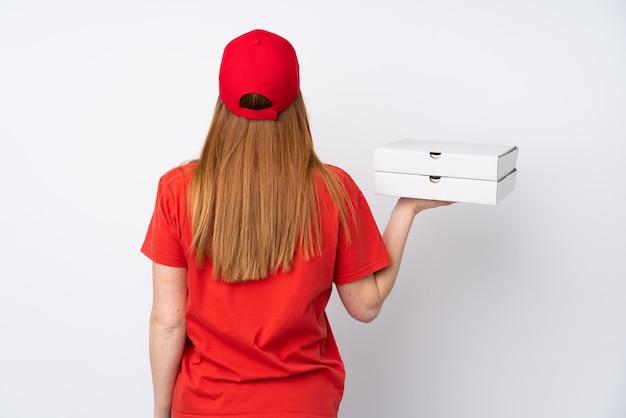 Mulher de entrega de pizza segurando uma pizza sobre parede rosa isolada em posição traseira