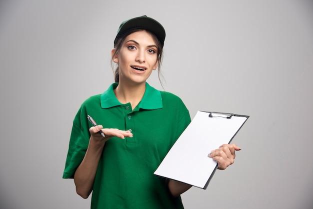 Mulher de entrega de uniforme verde, segurando a prancheta.