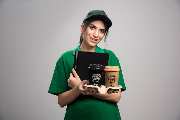 Mulher de entrega de uniforme verde segurando xícaras de café e prancheta.