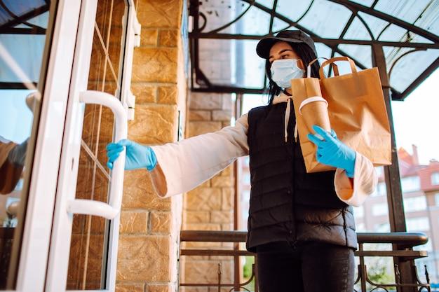 Mulher de entrega em máscara protetora e luvas com um saco de comida e café, abrindo uma porta para o edifício