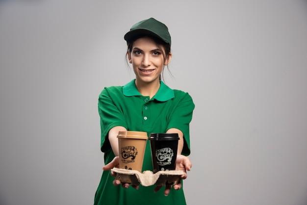 Mulher de entrega em pé com xícaras de café.