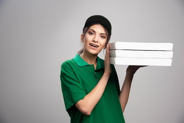 Mulher de entrega posando com caixas de pizza.