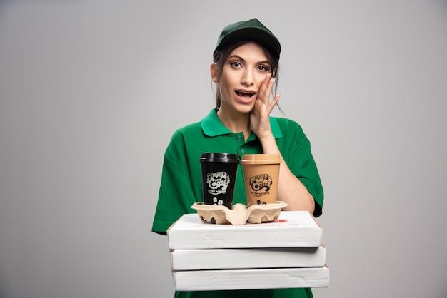 Mulher de entrega posando com xícaras de café e caixas de pizza.