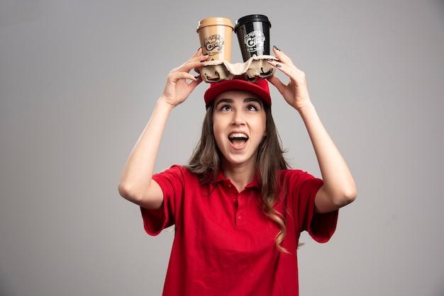 Mulher de entrega positiva segurando xícaras de café na cabeça.