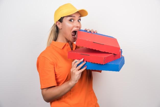 Mulher de entrega positiva tentando comer pizza no fundo branco.