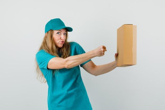 Mulher de entrega se preparando para dar um soco na caixa de papelão em t-shirt, boné e parecendo divertido.
