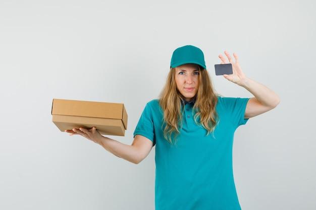 Mulher de entrega segurando caixa de papelão e cartão em t-shirt, boné e olhando alegre.