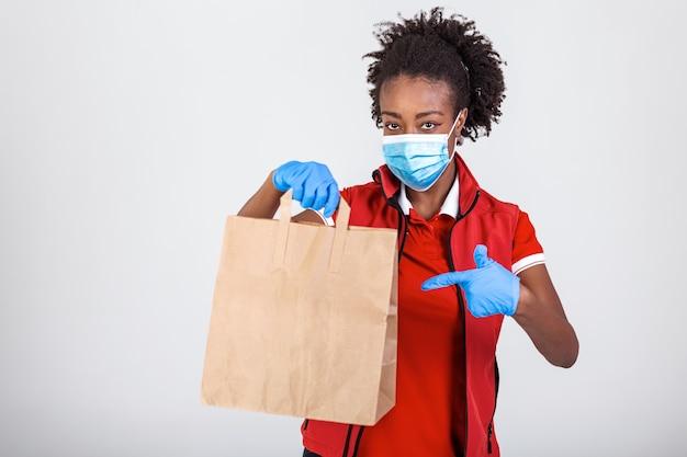 Mulher de entrega segurando um saco de papel em luvas de borracha médicas e mascarando o polegar. copie o espaço. transporte de entrega rápido e gratuito