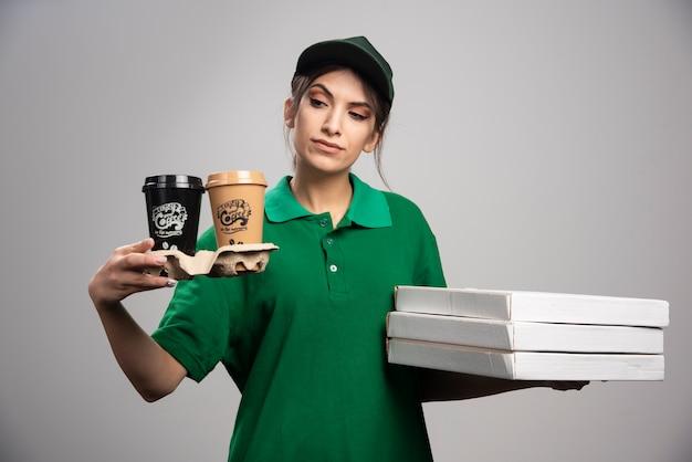 Mulher de entrega segurando xícaras de café e caixas de pizza.