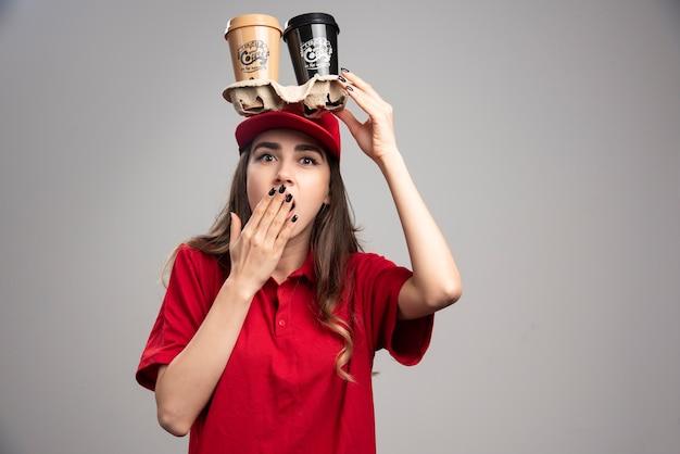 Mulher de entrega segurando xícaras de café na cabeça.