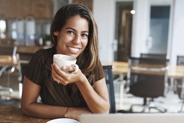 Mulher de escritório bonita e elegante tomando café quente, segurando uma xícara de café sentada sozinha