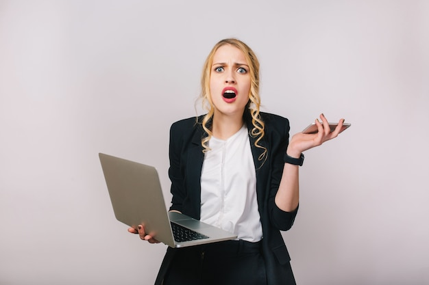 Mulher de escritório bonita loira moderna de retrato na camisa branca e jaqueta preta. trabalhando com laptop, telefone. surpreso, chateado, problemas, expressando emoções verdadeiras, estando ocupado