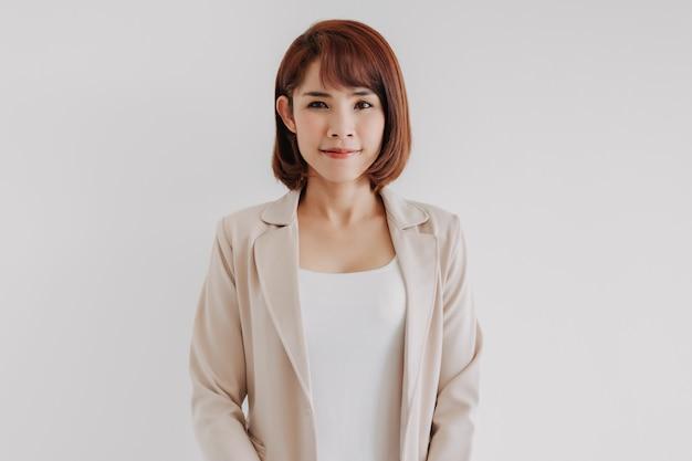 Mulher de escritório com roupas brancas e terno casual cremoso em fundo branco