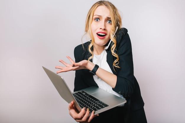 Mulher de escritório loira engraçada moderna de retrato na camisa branca e jaqueta preta. trabalhando com laptop, estando ocupado, falando ao telefone, surpreso, problemas, expressando emoções verdadeiras