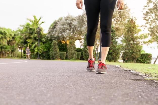 Mulher de esporte caminhando em direção ao lado da estrada. conceito passo