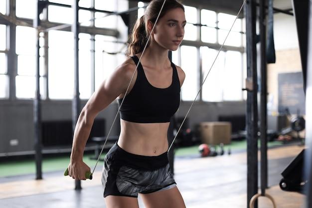 Mulher de esporte fazendo exercício na máquina de simulação do esquiador no ginásio.